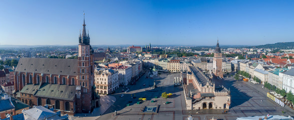 Aerial panorama of Krakow old city, Poland. Main Market Square (Rynek), old cloth hall (Sukiennice), town hall tower, St. Mary church (Mariacki), renovated Mickiewicz statue and far view of Wawel