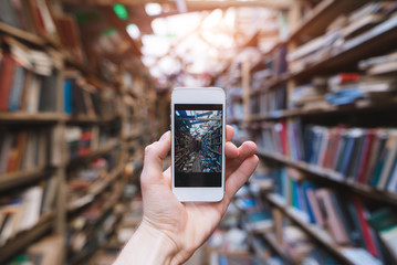 Human hand makes a photograph of a public library on a smartphone camera. Smartphone with library on screen.