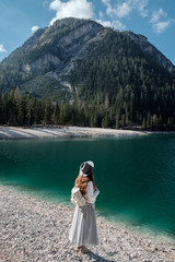A girl in a hat and a long dress is walking along the lake. Lago di Bries in the north of Italy