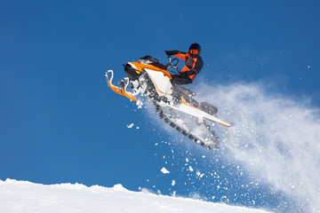 the guy is flying on a snowmobile on a background of blue sky leaving a trail of splashes of white snow. bright snowmobile and suit without brands.