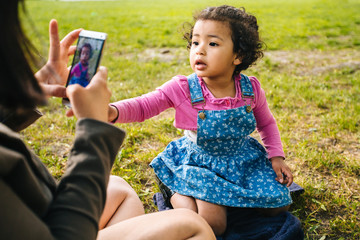 Unrecognizable mixed race mother taking a photo her a three years old dark skinned cute baby girl with smartphone in grass at summer park. Digital family memories concept.