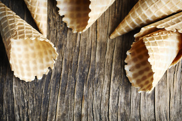Sweet wafer cone for ice cream on wooden background.