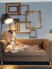 Femme sur canapé doré
