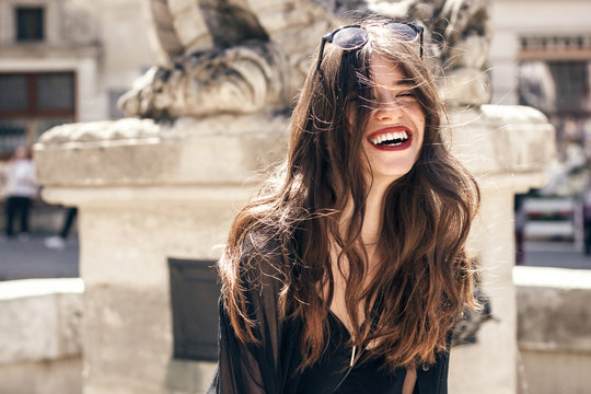 happy stylish woman with gorgeous smile and hair, having fun in sunlight in city street. beautiful hipster girl in fashionable outfit, waving hair and smiling. luxury look. carefree and happiness