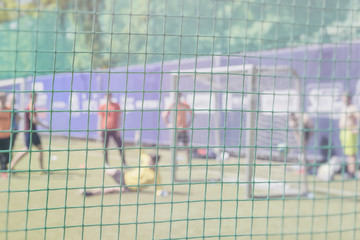 Fight for a soccer ball at the sports gate. Football training on sports field. Sportsmen, football players on training. Football outdoor stadium. Blurred image