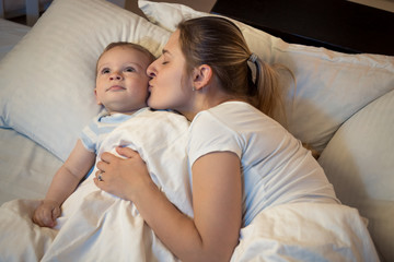 Portrait of loving young mother kissing her baby son before going to sleep