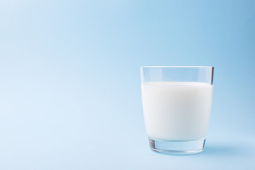 Milk in a glass on a blue background