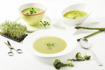 Broccolicreme-Suppe mit frischer Kresse, Spargelcreme-Suppe und Kräutersuppe auf weissem Hintergrund
