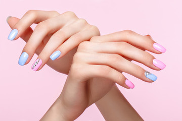 Foto op Plexiglas Manicure Beautiful pink and blue manicure with crystals on female hand. Close-up. Picture taken in the studio