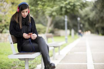 donna vestita di nero in una panchina sorride con cuffie con bandiera UK ascolta la musica al parco  e fa il gesto di OK