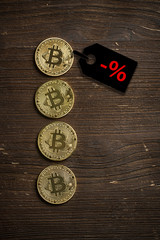 Bitcoin Münzen auf Holzuntergrund mit Preisnachlass-Hinweis