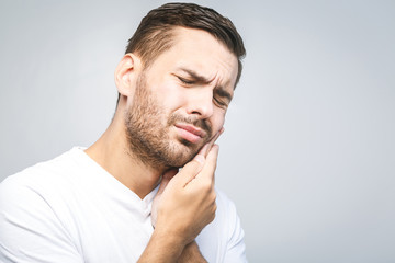 Toothache. Handsome young man suffering from toothache, closeup, touching his cheek to stop pain against white background. Strong toothache
