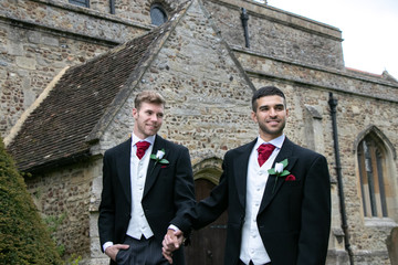 Gay wedding, grooms leave village church after being married with big smiles and holding hands