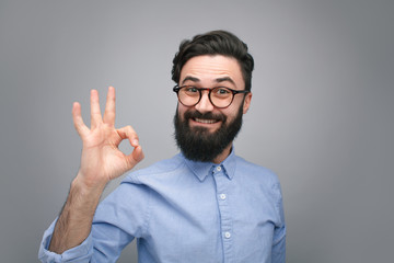 Handsome young man showing OK gesture