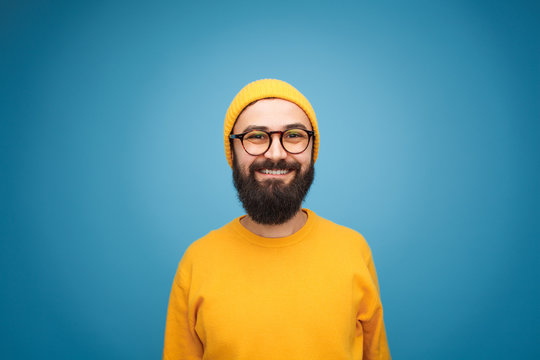 Smiling happy bearded hipster on blue