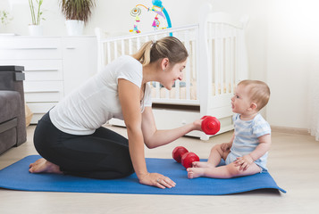 Beautiful young mother teaching her baby son doing fitness at home