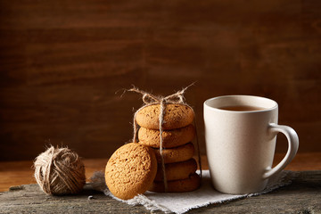 Traditional Christmas tea concept with a cup of hot tea, cookies and decorations on a wooden table, selective focus