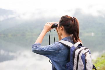 Thai adventure girl watching with binoculars