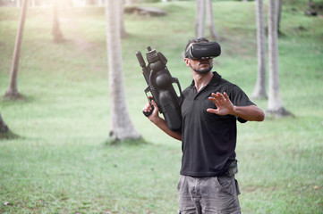 Man in virtual reality headset playing video game outdoors