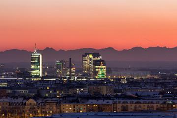 Rot leuchtender Abendhimmel über München mit den Bergen im Hintergrund