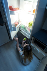 Yougn woman felt hungry at night sitting on kitchen floor and looking in refrigerator