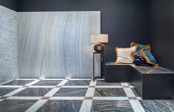 A modern interior of the living room in the black and white color with natural marble on the floor and on the wall