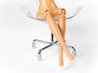 The beautiful slender legs of pretty figure girl doll doing gestures sexy on chair isolated on white background
