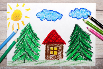 Photo of colorful drawing: small house surrounded by coniferous trees. House with red roof in forest.