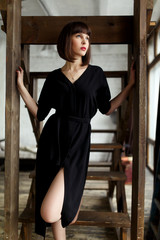 Image of young brunette in black dress near stairs against white brick wall