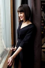 Photo of young brunette in black dress near window