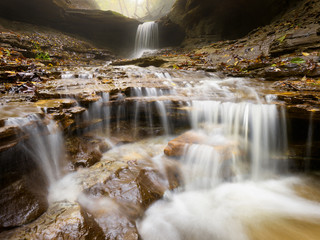 Silky Waterfall: Long exposure of natural flowing water over rocks in autumn