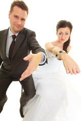Bride and groom in handcuffs wearing wedding outfits