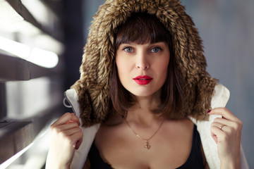 Photo of young brunette in jacket with fur hood