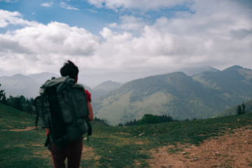 Incredible mountains. Portrait of a guy with a backpack from behind. Focus on the mountains