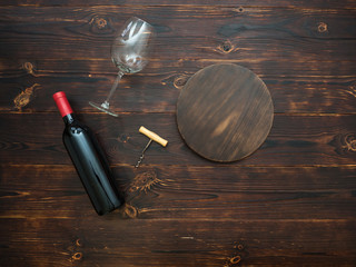 Bottle of red wine, a glass and a corkscrew on the table