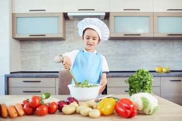 A boy dressed as a cook cooks in the kitchen.