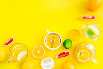 Brew fruit tea. Teacup and teapot near orange, lime, lemon, grapefruit on yellow background top view space for text