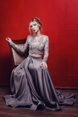 fashion studio photo of beautiful young girl with brown hair wearing luxurious beige dress,