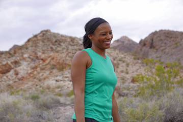 Woman in fitness top smiling outdoors