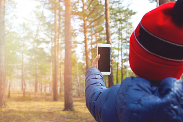 The child spends personal time in woods doing photographing the environment. Little nature Explorer taking pictures with a smart phone.