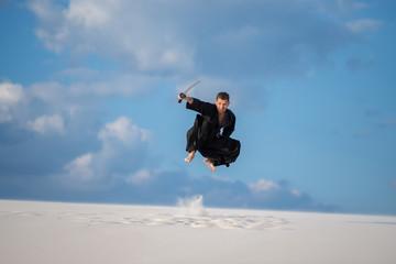Expressive man jumps with a Japanese sword, katana