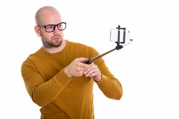 Studio shot of young bald muscular man