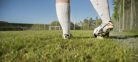 Im Sommer spielt ein Mann ganz alleine mit einem Fußball. Er steht an der Außenlinie und schießt den Ball.
