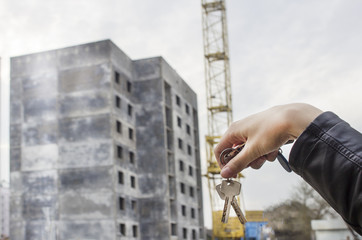 Construction of a residential house, a female hand holds the keys to the apartment