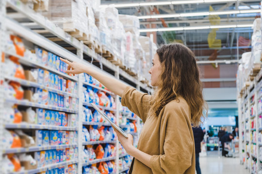 Young business woman with a tablet selects household chemicals in a supermarket
