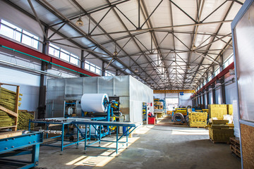 Thermal insulation production line. Machine tools for production of sandwich panels, roller conveyor in workshop, industrial interior, large hangar