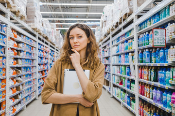 Business woman is thinking about shopping with a tablet in hand in a supermarket