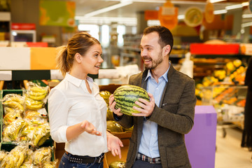 Couple with products in fruit department