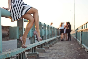 Young girl in a short dress and shoes is sitting on a bridge. Concept of envy, gossip, women's problems or the holiday of a hen party, birthday