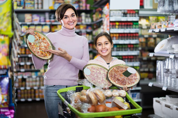 smiling woman with daughter choosing pizza in supermarket